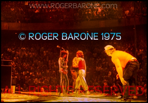 Rolling Stones' security member, Bob Bender, pursues a fan who leaped on stage near Jagger (6/29/75) © roger barone 1975