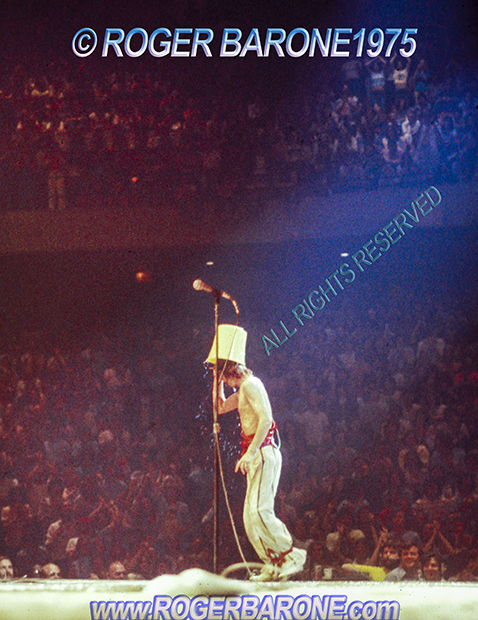 Mick Jagger pouring bucket of water on his head. Spectrum Arena © roger barone 1975