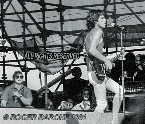 Rolling Stones' security team member, Bob Bender, watching over Mick Jagger. Philly, (9/25/81) © Roger Barone